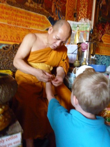 We were blessed by a monk and sprinkled with Holy Water. We then each received a bracelet made from Holy Cotton. Here is the monk putting on Beckett's bracelet.